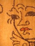 Close-up of a painting. The face seems to be made of words