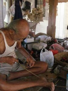 I Wayan Tangguh at work weaving horse hair into strands for masks.