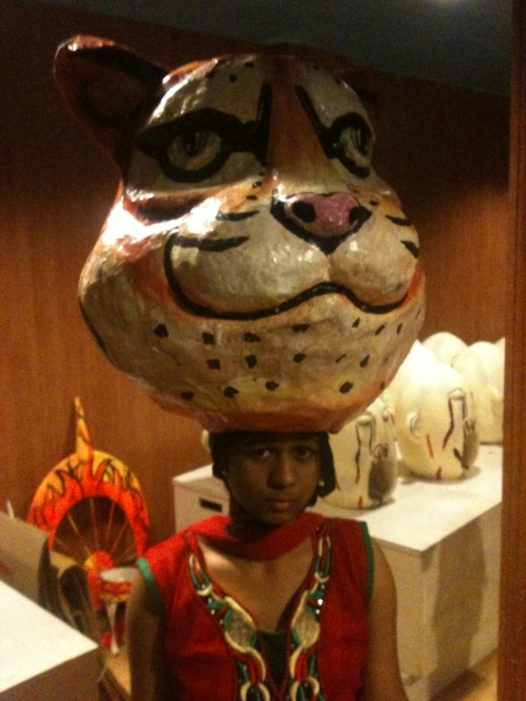 Mama Tiger with ears and paint. atop a bike helmet, atop an actor.