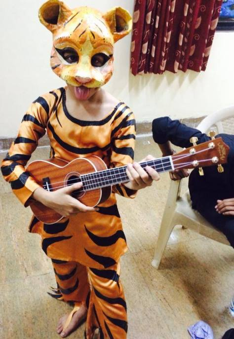 Baby tiger playing ukelele? I'd pay to see this show.